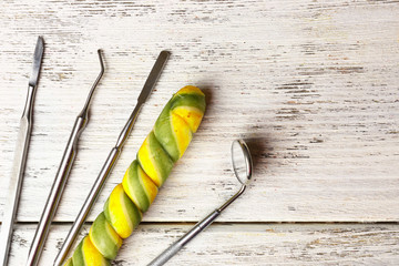 Dentist tools with lollipop on wooden background