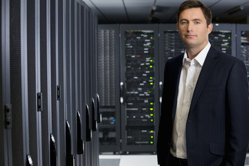 Manager, looking at camera, in server room