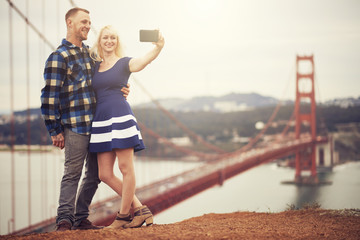 couple in taking selfie in front of golden gate bridge