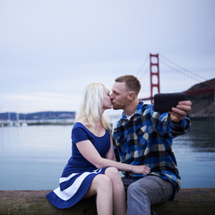 couple kissing and taking selfie in front of golden gate bridge