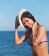 Carefree bikini woman on blue sea background smiling