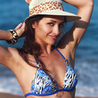 Happy woman in hat posing on blue sea background. Closeup