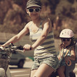 Smiling woman and kid riding in sun glasses. Vintage closeup
