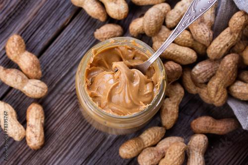 Fresh made creamy Peanut Butter in a glass jar - 78395767
