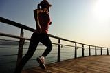 Fototapeta young fitness woman running on sunrise seaside boardwalk