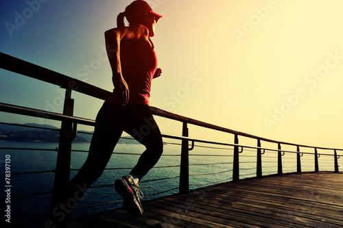 young fitness woman running on sunrise seaside boardwalk - 78397130