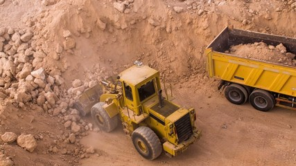 top view excavator loading crushed rock on dumper truck