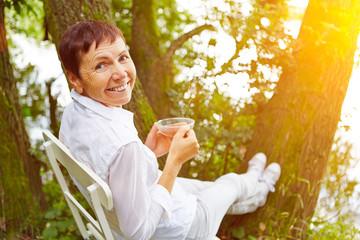 Seniorin macht Pause mit Tasse Tee