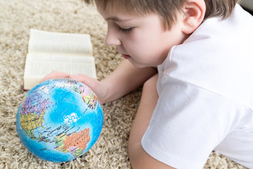 Boy studying the globe and reading  book