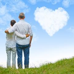 Paar Senioren schaut auf Herz im Himmel