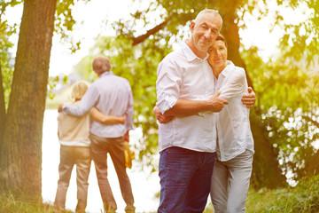Zwei Paare umarmen sich im Garten vom Seniorenheim