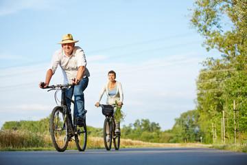 Senioren fahren mit Fahrrad durch Landschaft
