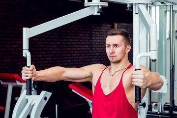 Young athlete on the simulator for the biceps chest.