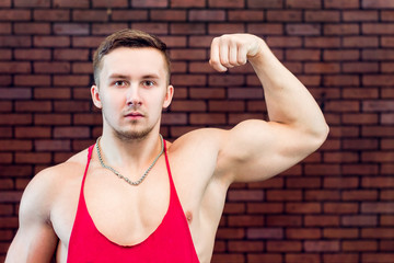 Beautiful , young athlete shows his inflated biceps.