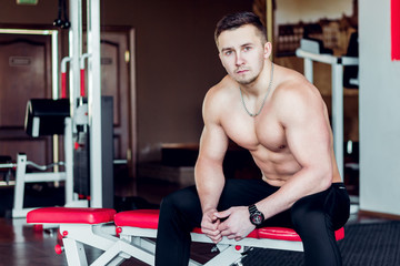 Young athlete sitting on a bench in the gym