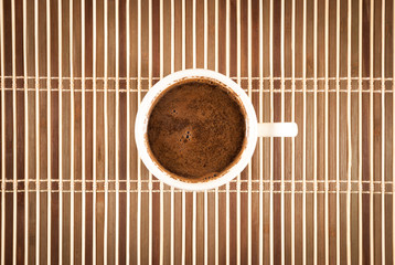 A cup of coffee on a bamboo background