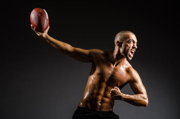 Muscular football player with ball