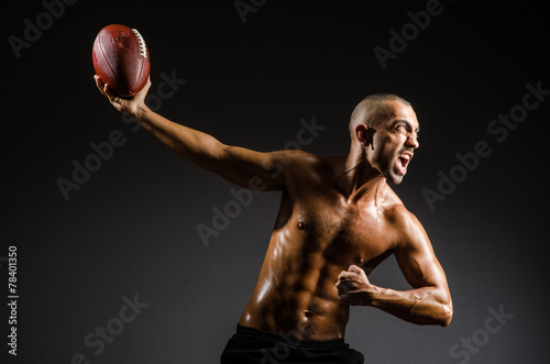 canvas print picture Muscular football player with ball
