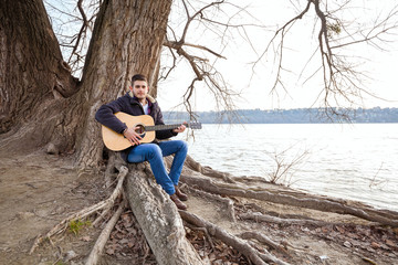 Young man sitting on a tree and playing guitar