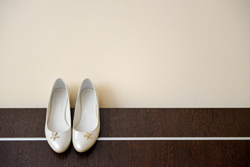 White shoes of bride clings to the edge bed