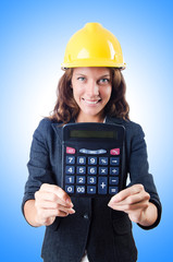 Female builder with calculator on white