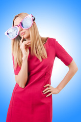 Tall model with giant sunglasses on white
