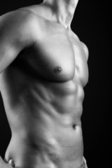 Fitness man posing on black background