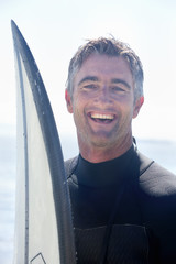 Portrait of surfer with surfboard, smiling at camera