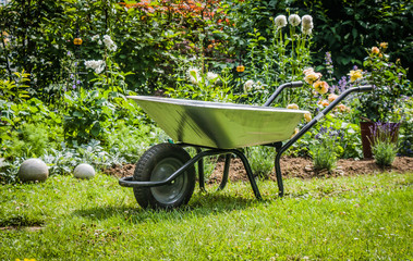 Wheelbarrow on the front of flower bed .