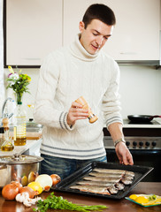 man adding spices in raw fish