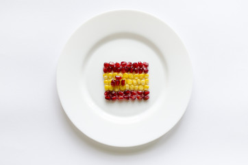 Creative flag of Spain from corn and pomegranate on white round