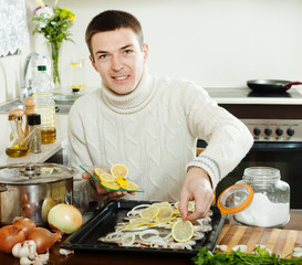 Handsome guy cooking trout fish with lemon