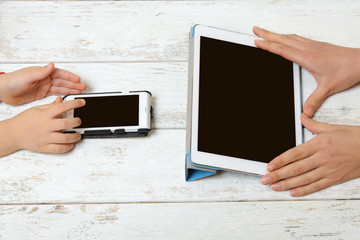 Mother and child are holding tablet and phone