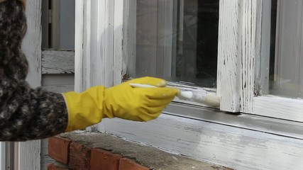 Home renovation, old wooden window painting with paint brush