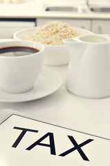 tax written in the screen of a tablet, on a set table for breakf