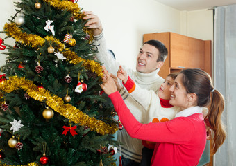 parents and baby girl decorating Christmas tree