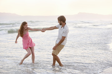 Couple, playfully pulling each other into the sea on sunny beach