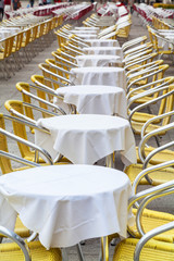 Tables and yellow chairs in the terrace of a bar.