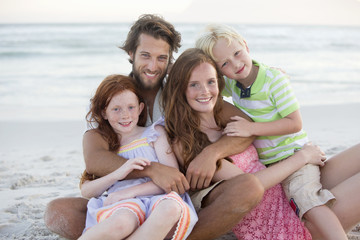 Portrait of family, smiling at camera, embracing on sunny beach