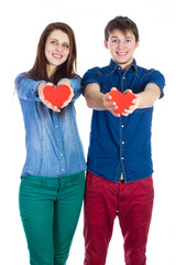 Beautiful young couple holding a small red paper heart in hands