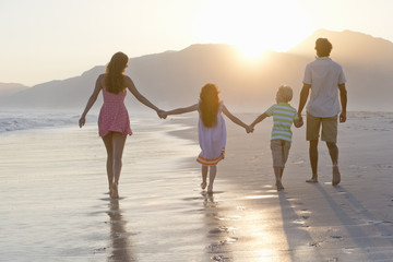 Happy family walking into distance, holding hands, on sunny beach