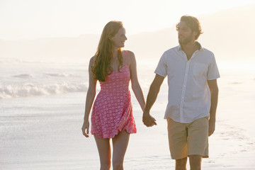 Couple, holding hands, walking along sunny beach