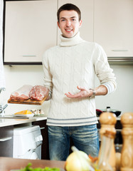 Ordinary man holding raw meat  in itchen