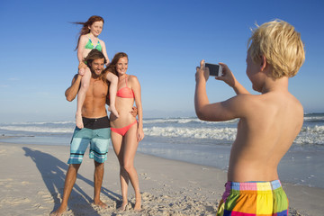 Boy taking photo of mother, father and sister on sunny beach