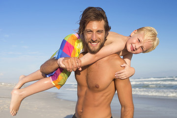 Portrait of father with son on shoulder on sunny beach