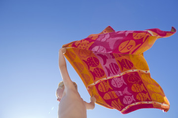 Portrait of boy holding towel above head in the wind on sunny beach