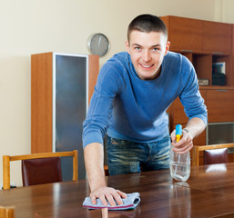 Smiling man cleaning  furniture with rag