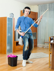 Happy man washing  floor with mop in home
