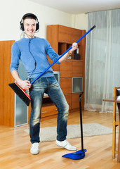 Young cheerful man cleaning and playing with broom in living roo