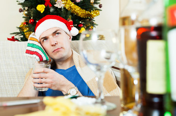 Suffering guy in Santa hat with glass of water